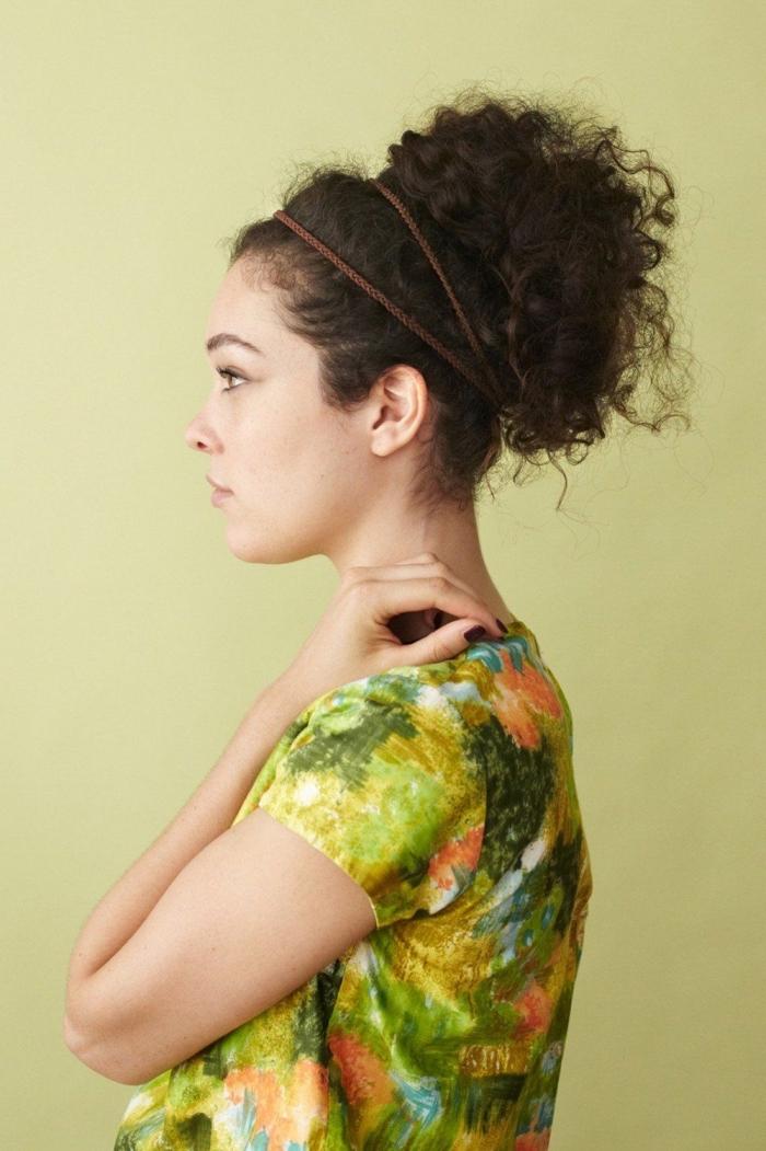modèle de coiffure simple avec un élastique autour de cheveux attachés en chignon haut décontracté pour cheveux crépus