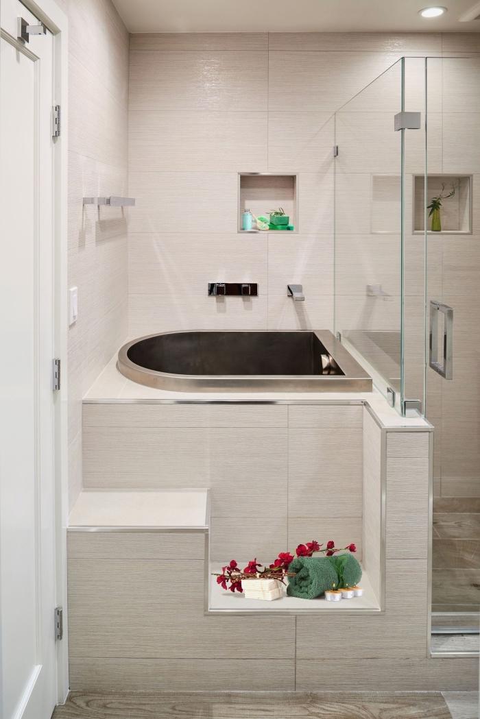 déco de salle de bain style moderne avec carrelage beige et mini baignoire à finition métallique, idée rangement gain place avec niches murales