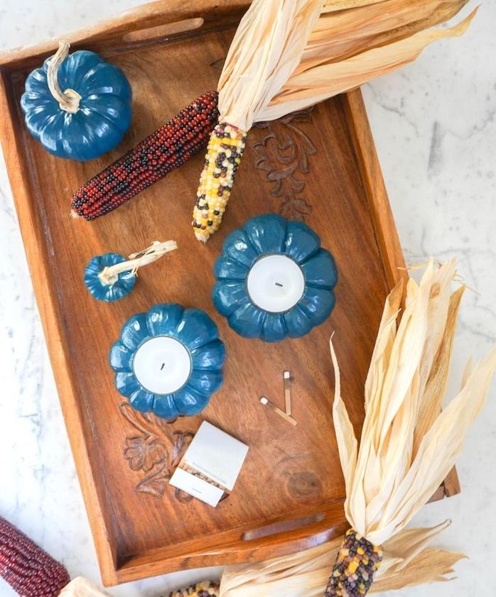 bougeoirs DIY a faire soi meme, mini citrouille repeinte en bleu avec une bougie à l intérieur et mais dans une cagette de bois marron