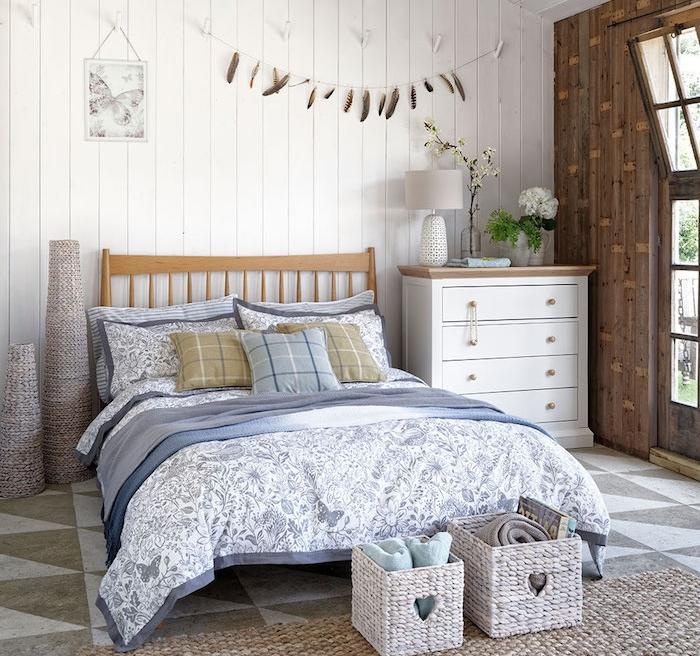 lambris blanchi, lit en bois, linge de lit blanc et bleu, tapis à grosses mailles, commode blanc, paniers de rangement bout de lit, deco murale plumes, deco de charme