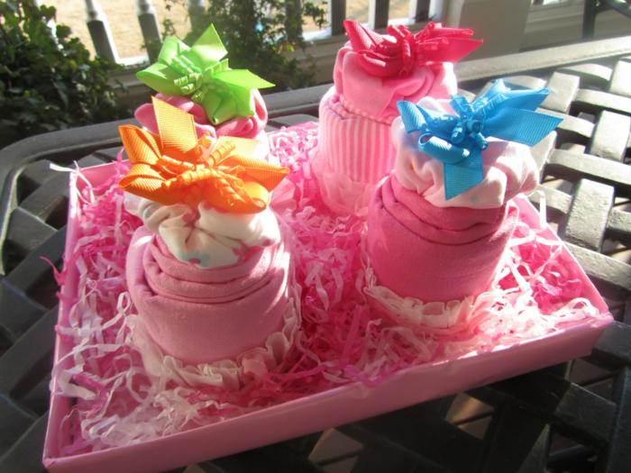 baby shower fille, chaussettes roses enroulées comme des cup cakes, boite rose, nœuds en orange, vert pomme, leu pastel et rouge