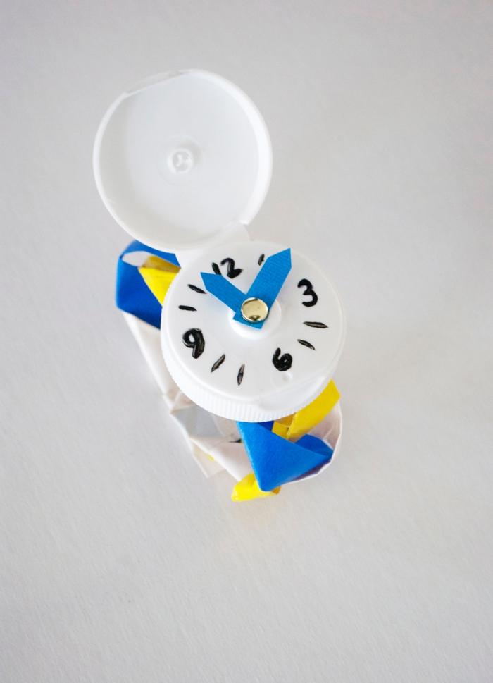bricolage récupération à faire avec les enfants, réaliser une montre originale avec une capsule de bouteille en plastique et du papier coloré