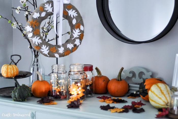 deco en bocaux de verre remplis de feuilles d automne, citrouilles et couronne enveloppée de jute grise et motif feuilles d automne en feutrine
