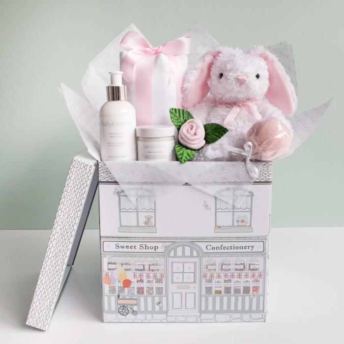 baby shower garcon, lapinou en peluche rose, boite en carton qui imite une grande maison, avec toit, et des magasins au sous-sol