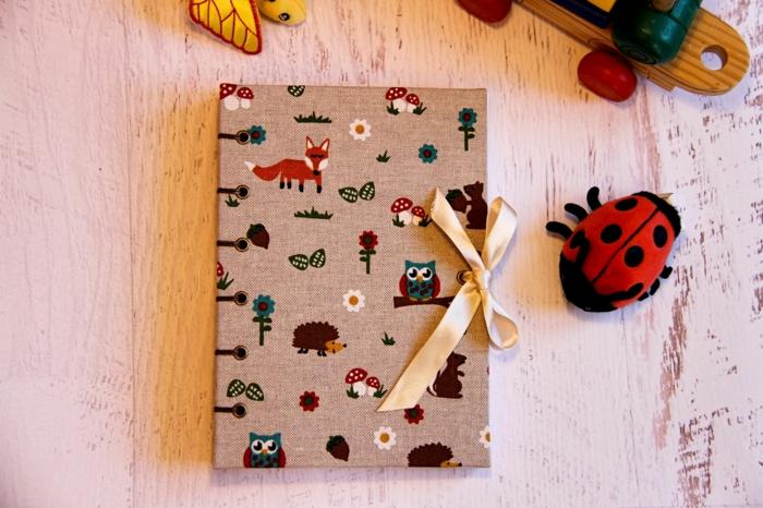 agenda bébé revêtue en tissu beige en lin avec des motifs animaux de la foret, coccinelle en peluche, table avec plan en bois vieilli blanc, baby shower garcon