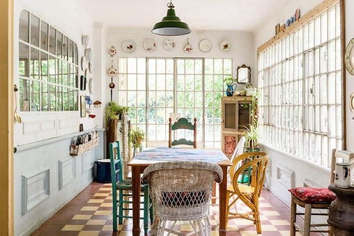 modele de salle à manger dans une maison de campagne avec des chaises vintage dépareillées, sol damier, deco murale vaisselle shabby, table bois avec nappe fleurie
