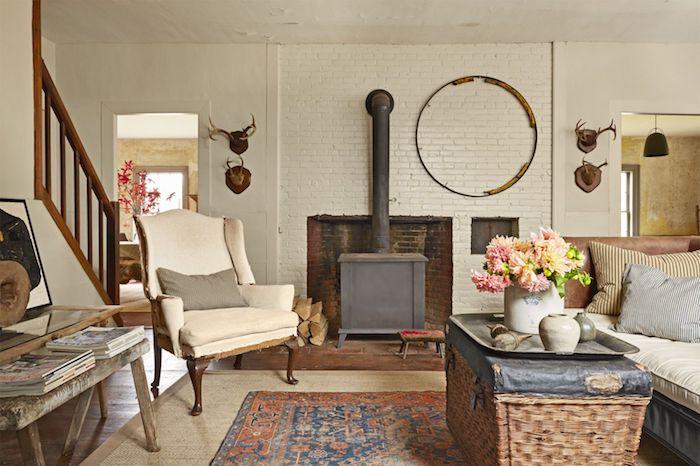 mpodele de salon chaleureux e accueillant deco campagne avec canapé en cuir marron, table en coffre de rangement, tapis vintage, cheminée ancienne