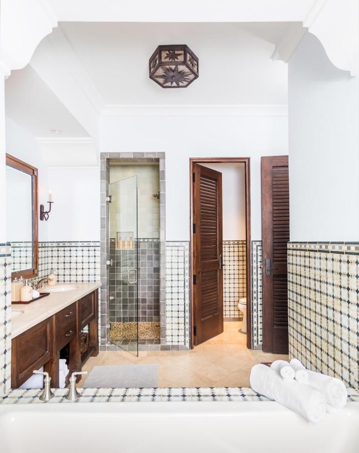 une salle de bain carreaux de ciment de style espagnole posés en guise de soubassement qui s'accorde parfaitement avec l'aspect antique du meuble salle de bains