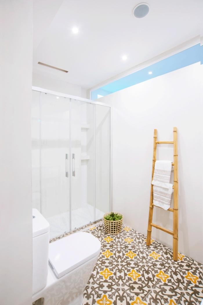 salle de bain monochrome avec douche à l'italienne au sol en carrelage carreaux de ciment à motifs vintage jaune et marron qui réchauffe l'ambiance épurée