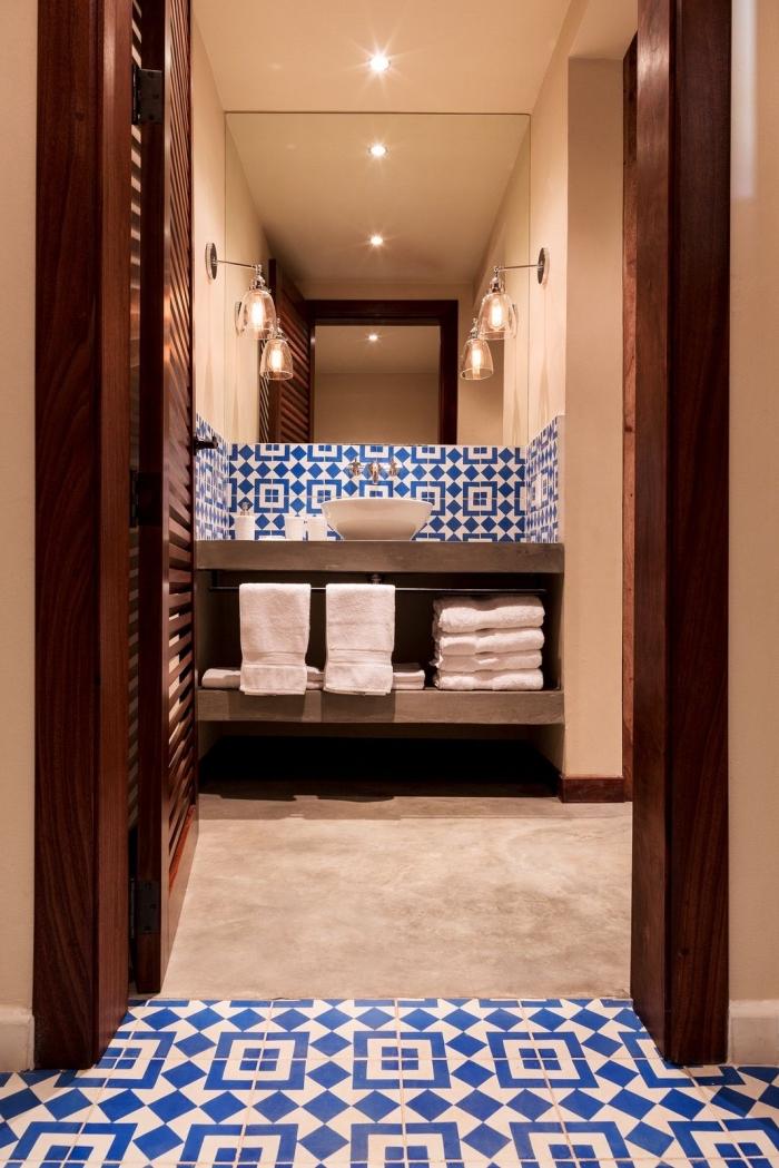 une faience carreaux de ciment posé en crédence derrière la vasque à poser en jolis motifs géométriques en bleu roi