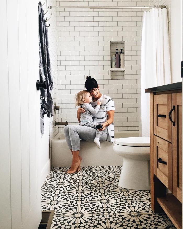 carrelage effet carreaux de ciment à motifs floraux noir et blanc qui s'harmonise avec le carrelage métro de l'espace douche et dynamise l'ambiance monochrome