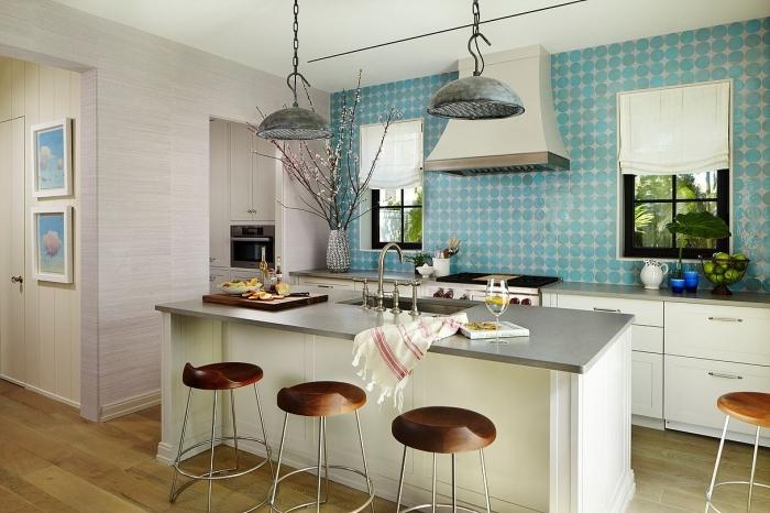 cuisine avec ilot central de lavage qui joue le rôle d'une surface de travail et d'un coin repas avec ces trois tabourets de bar en bois et métal