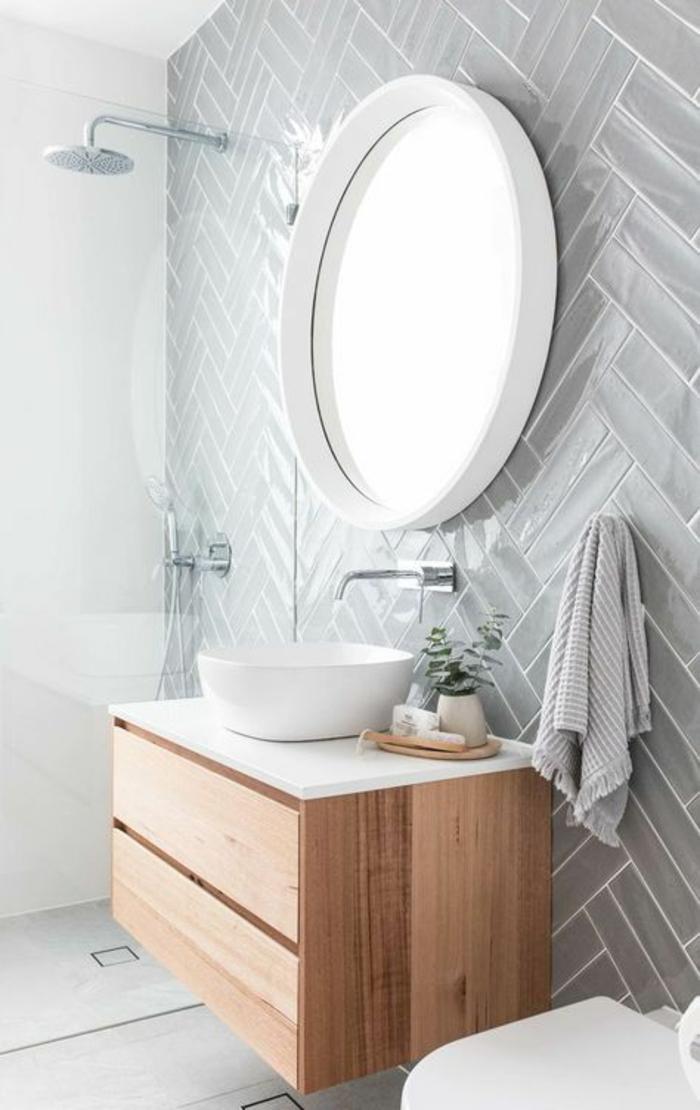 salle de bain 4m2, murs en couleur gris perle, miroir rond au cadre blanc, douche italienne en petit espace, meuble suspendu en beige