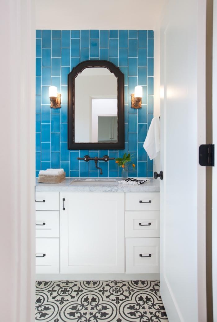 carreaux de ciment noir et blanc à jolis motifs arabesques en contraste avec le carrelage métro bleu derrière le lavabo