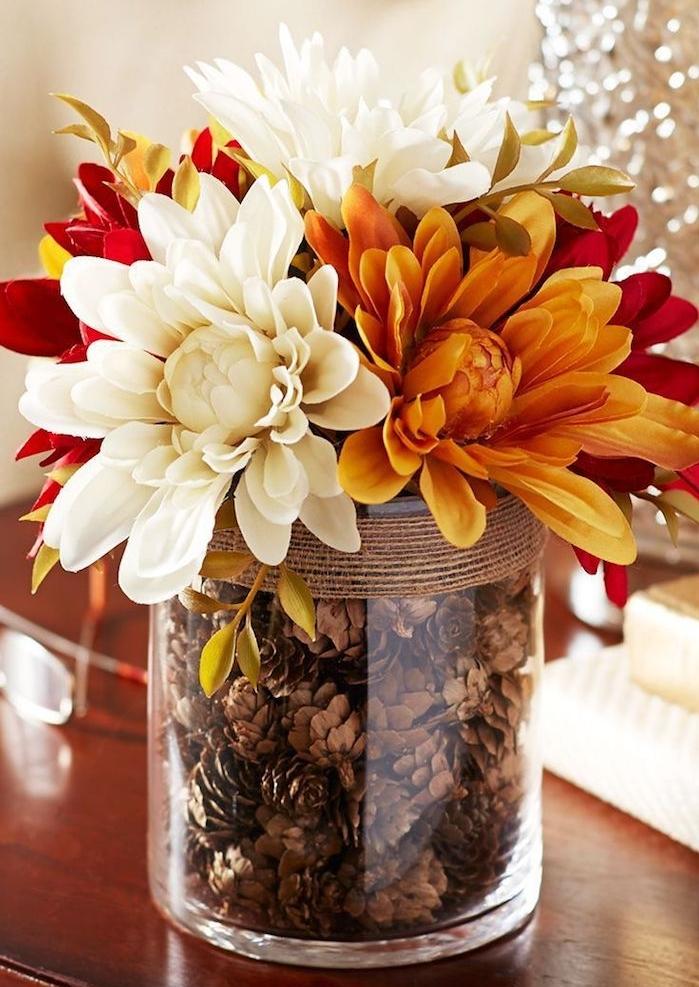 centre de table automne en vase de verre rempli de pommes de pin et décoré de ficelle, fleurs d automne