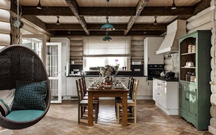 déco cocooning dans une cuisine traditionnelle aux murs en bois avec plafond en poutres de bois apparentes et carrelage de sol beige