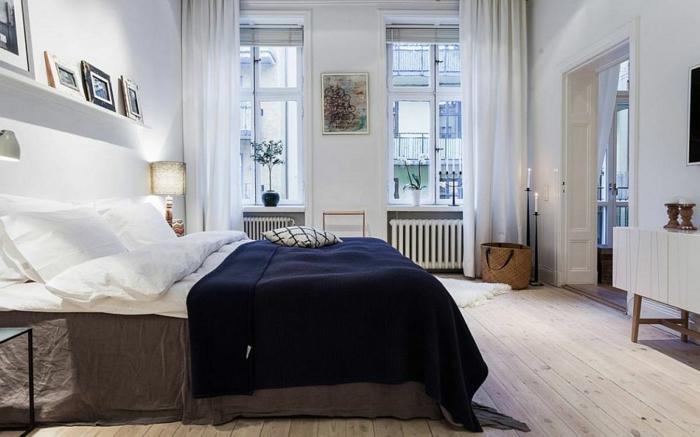 peinture bleue pâle, étagère blanche, bougeoirs élégants, plaid de lit bleu, rideaux blancs, sol planches de bois clair