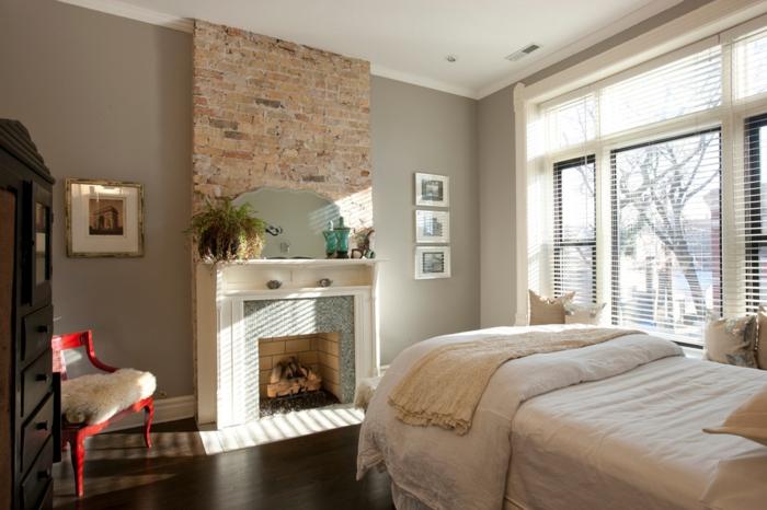 chambre à coucher, cheminée blanche, chaise rouge, murs gris, commode noire, manteau de cheminée briques