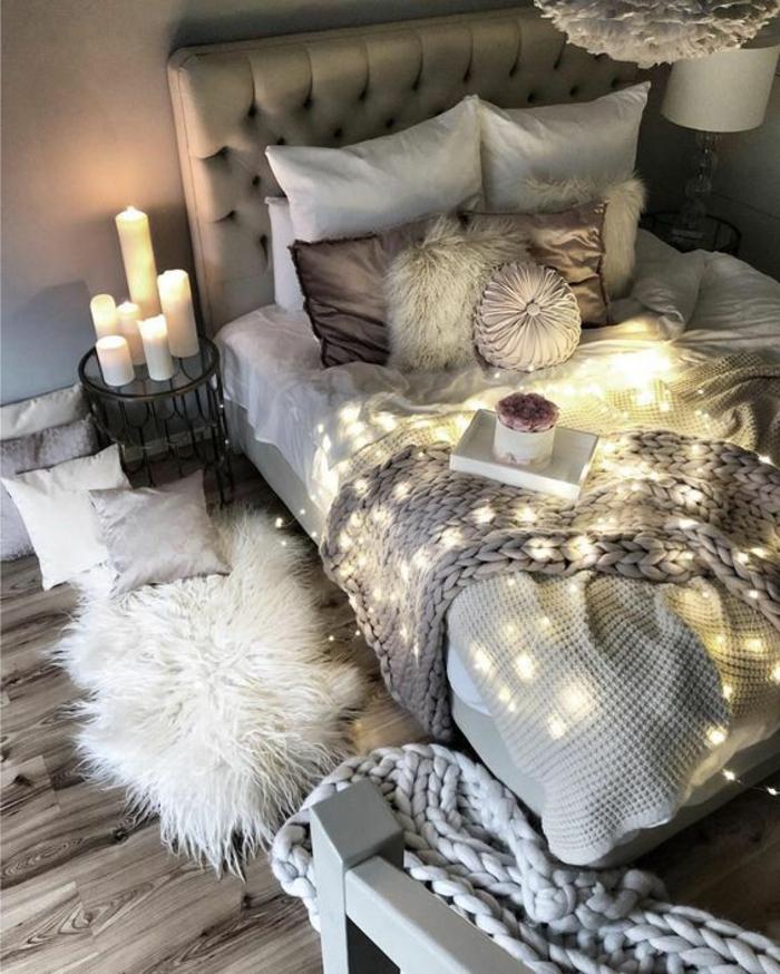 fourrure blanche, plaid tricoté gris, bougies blanches, guirlande lumineuse, plaid tricoté, petit tabouret métal, fourrure blanche