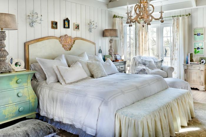 décoration chambre adulte moderne, chandelier somptueux, tête de lit blanc et doré, commode vert menthe, parement mural planches blanches