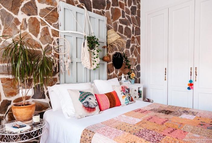 aménagement intérieur moderne dans la chambre à coucher aux murs en pierre avec meubles de bois et objets en macramé fait main, macramé suspension à design attrape-rêve avec plumes