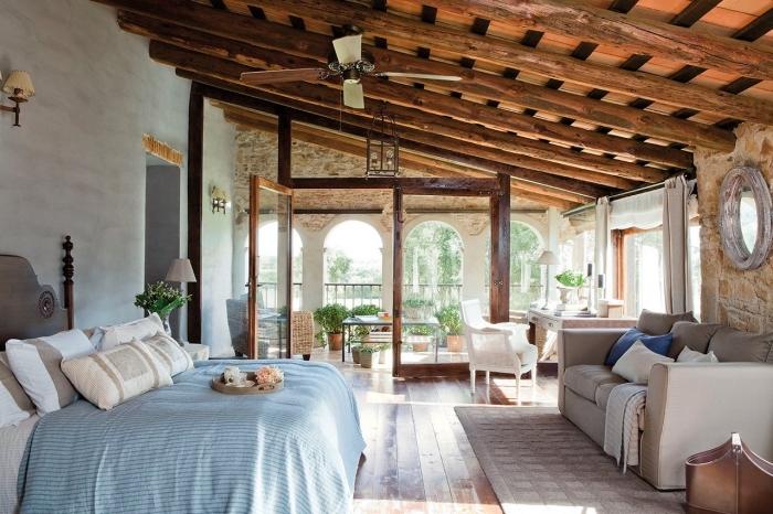 ambiance exotique dans une chambre à coucher au plafond en poutres de bois exposées avec meubles en bois et cuir