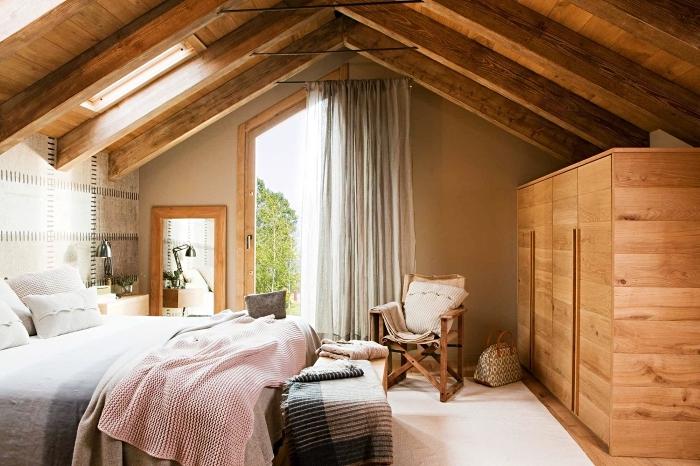 modèle de chambre rustique sous plafond avec poutres exposées et meubles de bois, idée comment aménager une pièce mansardée