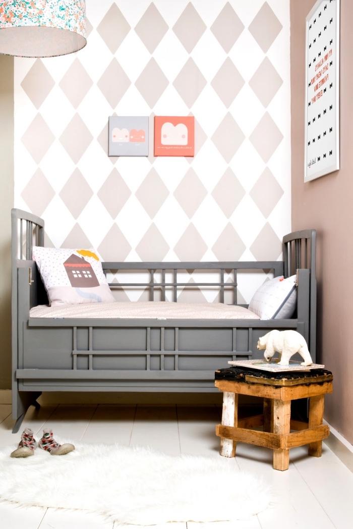 tapisserie moderne à motifs losanges en rose poudré posée sur une partie du mur pour délimiter le coin sommeil dans la chambre enfant vintage scandinave