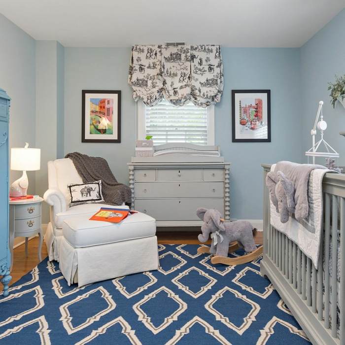 tapis bleu géométrique, fauteuil blanc, jouet éléphant, cadres peintures, commode gris clair