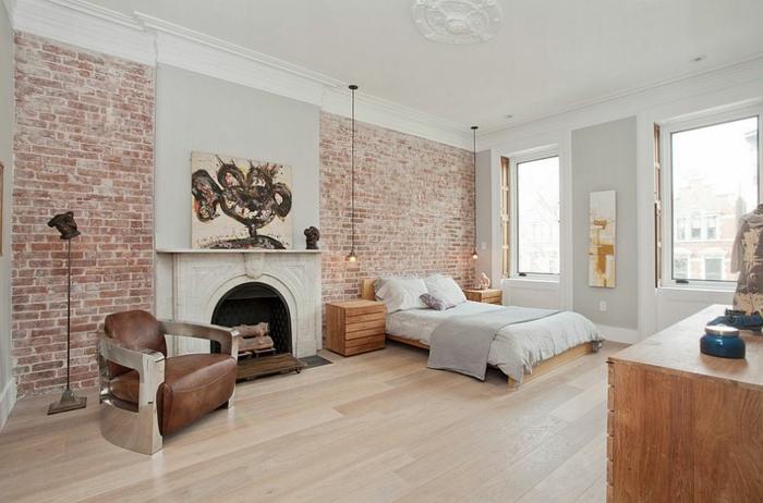 chambre spacieuse, mur en briques, fauteuil en cuir, cheminée décorative, ampoules suspendues, deco chambre romantique