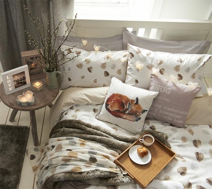 lit en blanc aux motifs dorés, plateau en bois avec petite déjeuner, petite table de bois avec bougeoirs romantiques, aménagement chambre scandinave