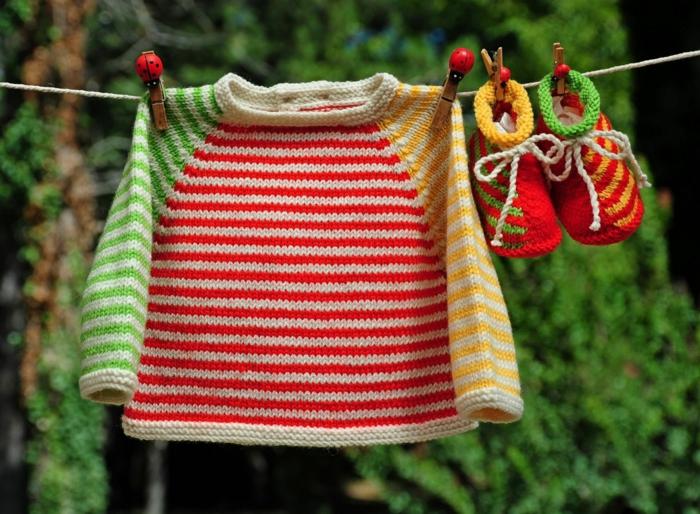 idée cadeau femme enceinte, chaussons colorés et veste colorée, suspendues sur un fil sèche-linge, avec des pinces en bois clair aux motifs coccinelles