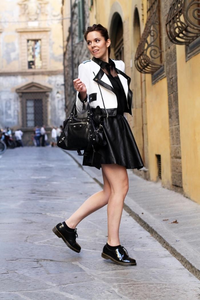 vision moderne chic femme en jupe simili cuir courte et une paire de chaussures derbies noires vernies, modèle de veste en cuir en blanc avec bordures en noir