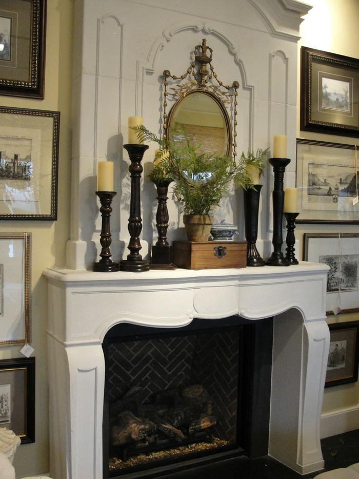 cheminée blanche, bougeoirs anciens noirs, miroir décoratif, cadres peintures