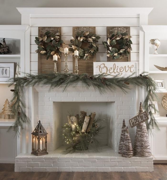 cheminée décorative blanche, bûches décoratives, couronnes de laurier, lanterne