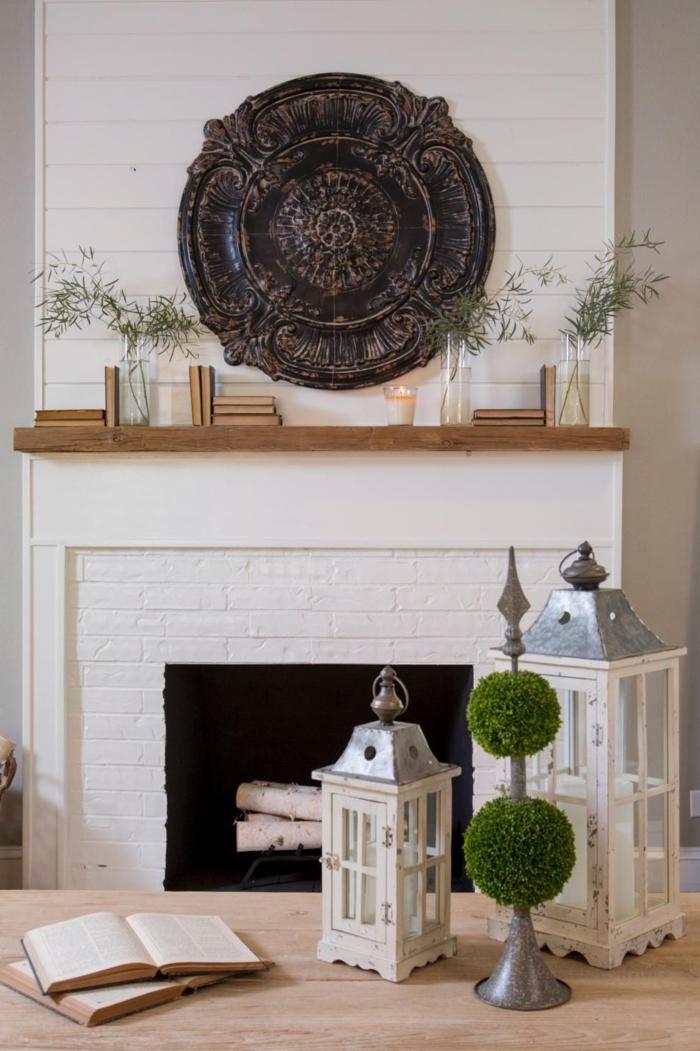 lanternes décoratives peintes blanches, table en bois avec livres vintage, lambris mural bois blanc, déco murale ronde