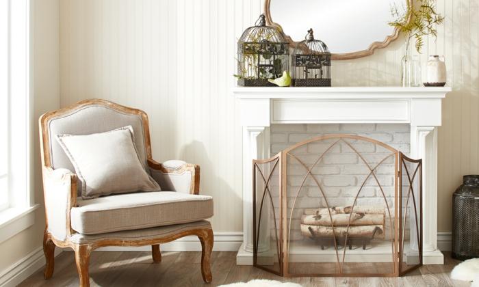cheminée blanche décorative, fauteuil à l'encadrement doré, cages décoratives noires