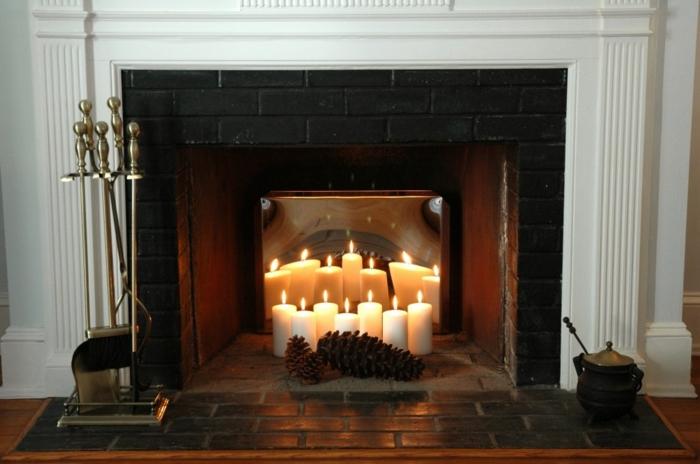 cheminée avec bougies blanches, carreaux noirs, cones et bougies allumées