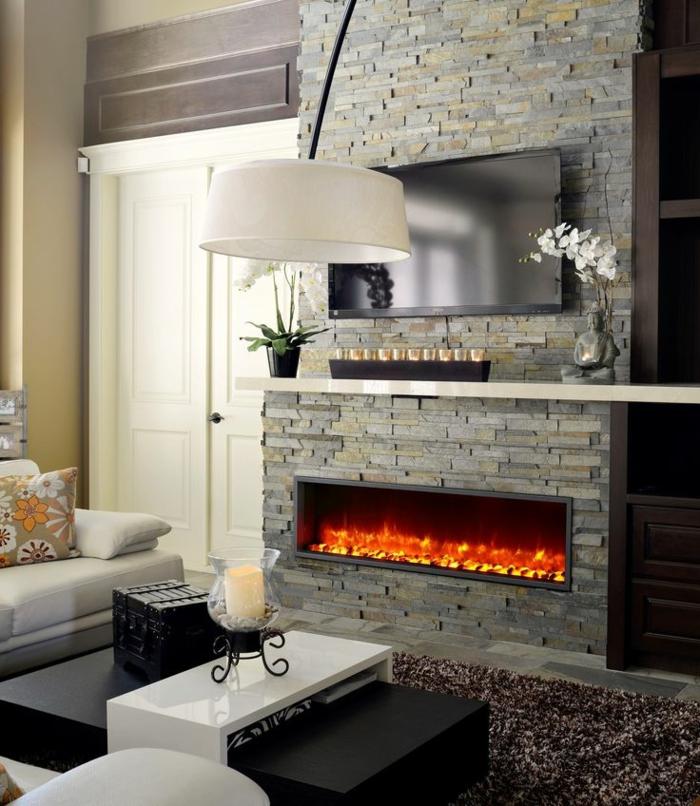 cheminée à effet flammes, manteau en briques grises, bougeoir décoratif sur une table basse blanche,