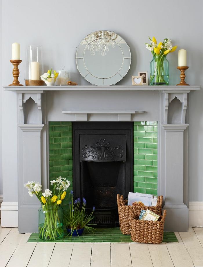 cheminée murale couleur gris clair, briques vertes, petit miroir rond, vases avec fleurs, paniers décoratifs