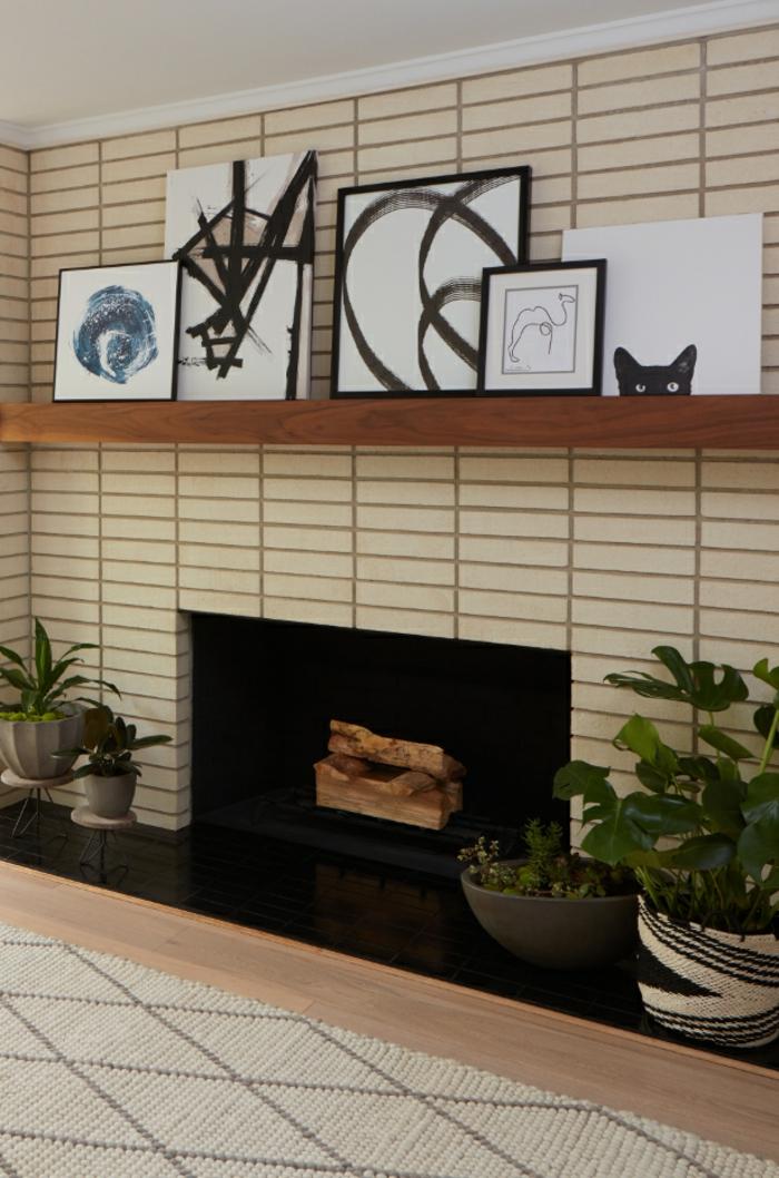tapis berbère, pots de fleurs, manteau de cheminée décorative beige, peintures noires et blanches