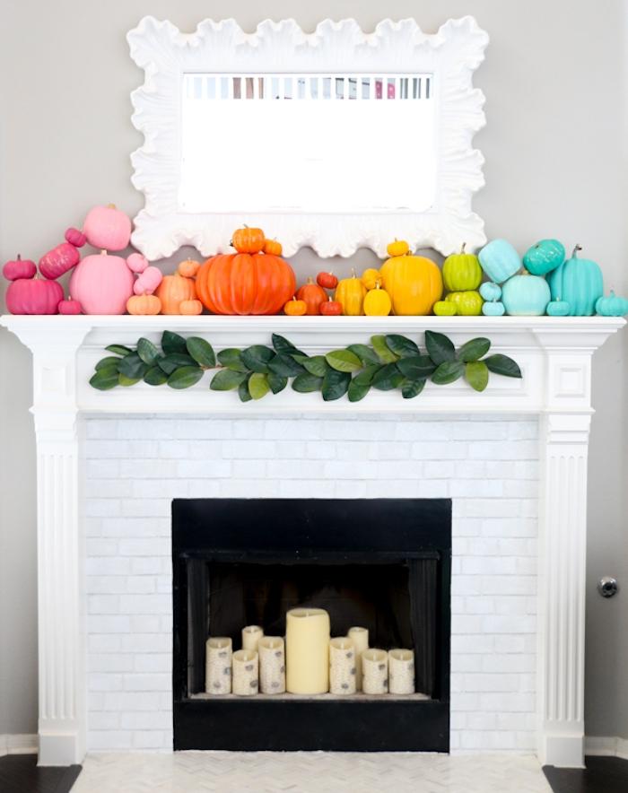 deco cheminée blanche décorée de citrouilles de tailles variées, guirlande de feuilles vertes et bougies décoratives