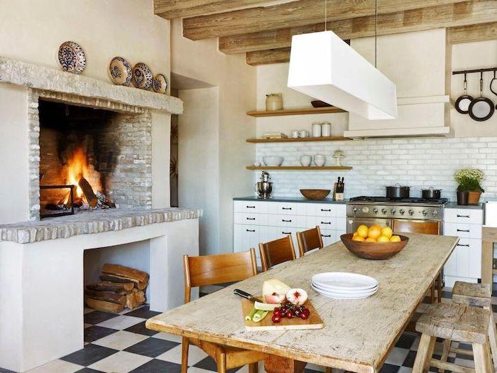 cheminée rustique, table et chaises bois brut, cheminée design vintage campagne, carrelage cuisine metro, meuble bas blanc, poutres apparentes