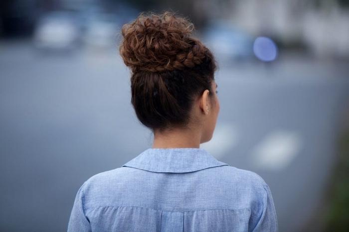 modèle de coiffure romantique sur cheveux longs crépus, chignon haut décontracté avec une couronne de tresse