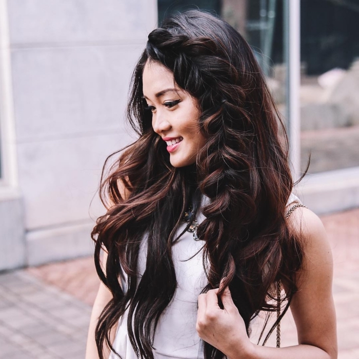 modèle de coiffure pour cheveux longs et volumineux naturellement ondulés avec une grosse natte de côté