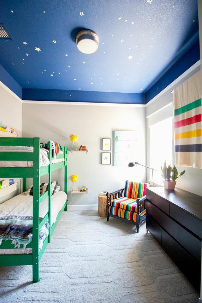 plafond bleu aux étoiles dans une chambre enfant garcon, lits mezzanine verts, fauteuil bariolé