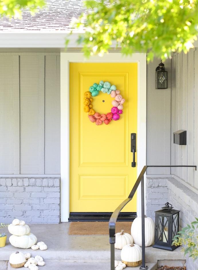 idee deco de porte en jaune avec une couronne de mini citrouilles colorées et des citrouilles de tailles variées sur les escaliers
