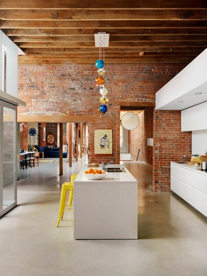 grand loft scandinave, poutres au plafond, tabourets tolix jaunes, bar de cuisine blanc, mur en briques, suspension originale
