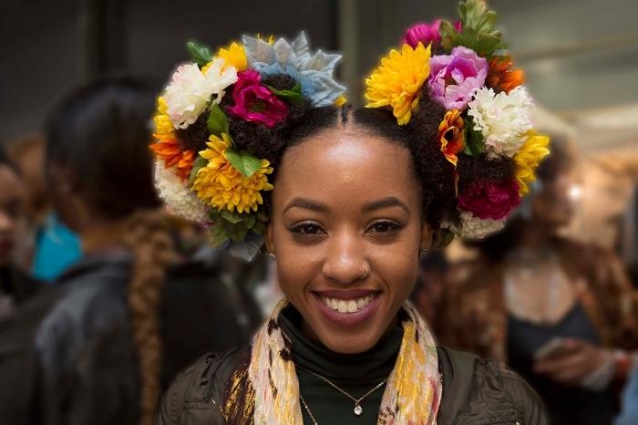 cheveux frisés femme, exemple de coiffure sur cheveux crépus attachés en deux couettes hautes ornées de couronnes florales
