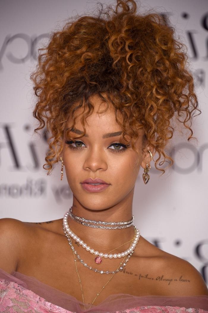 Rihanna aux cheveux longs de couleur châtain cuivré attachés en queue de cheval haute avec mèches tombantes sur le visage